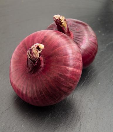 trivet: flat red onion on black slate stone surface Stock Photo