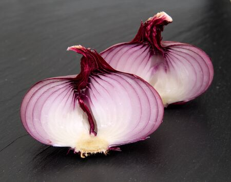 trivet: flat red onion cut in half on black slate stone surface Stock Photo
