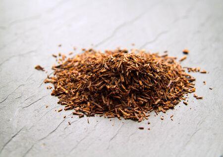 red bush tea: Rooibos tea, dry fermented  leaves on black slate surface