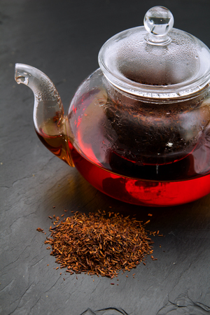 Rooibos tea, dry leaves and a small glass teapot brewing, on black slate surface
