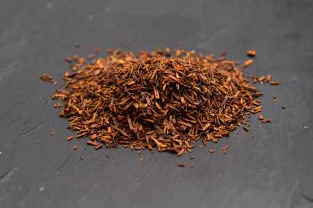 red bush tea: Rooibos tea, dry fermented  leaves on black slate surface