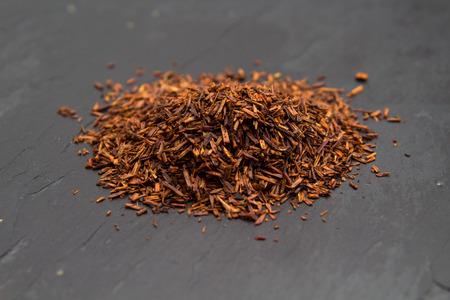 Rooibos tea, dry fermented  leaves on black slate surface