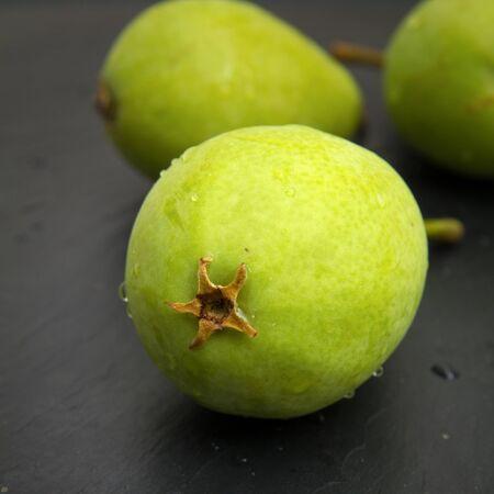 trivet: green pears on black slate surface