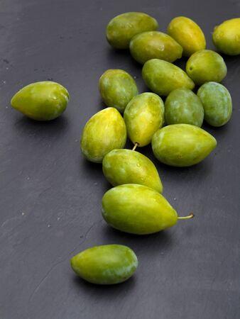 trivet: green plums on black slate surface