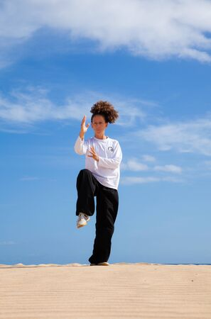 tai chi: Tai chi in the dunes - young woman in black and white making tai chi moves Stock Photo