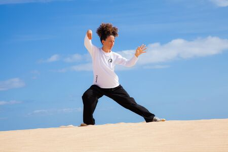 Tai chi in the dunes - young woman in black and white making tai chi moves photo