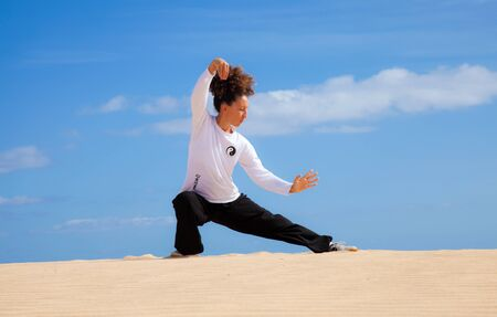 Tai chi in the dunes - young woman in black and white making tai chi moves Stock Photo