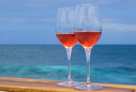 two glasses of rose wine on a wooden surface, blue ocean in the background Stok Fotoğraf