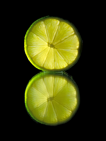 quartered: backlit lime pieces on black mirror Stock Photo