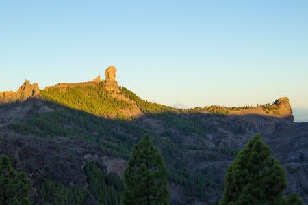 ghostlike: Gran Canaria, Caldera de Tejeda, sunrise hits  Roque Nublo  mountain range, rock formation El Fraile, The Monk, casts a ghost-like shadow