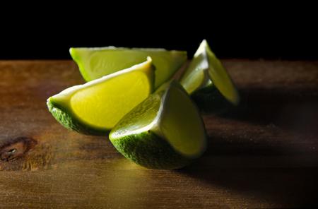 quartered: quartered lime fruit in dark wooden surface Stock Photo