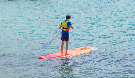 learning stand up and paddle  - teenager on a board 版權商用圖片