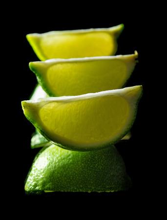 quartered: backlit quarters of lime fruit on black mirror
