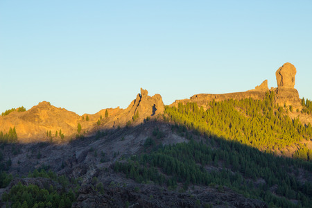 Gran Canaria, Caldera de Tejeda, sunrise hits  Roque Nublo  mountain range, rock formation El Fraile, The Monk, casts a ghost-like shadow