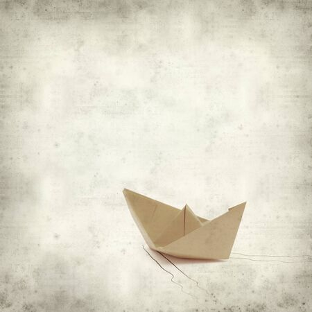 textured old paper background with origami paper boat