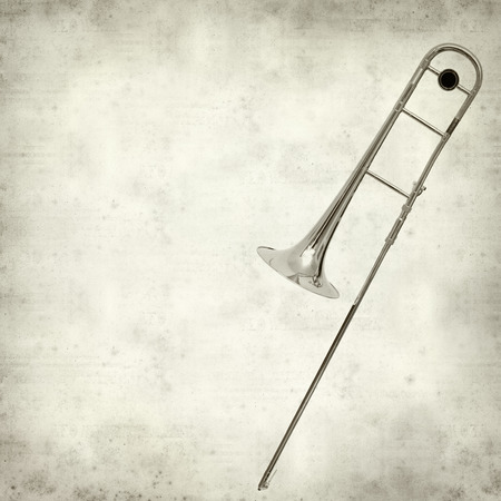 trombone: textured old paper background with silver trombone Stock Photo