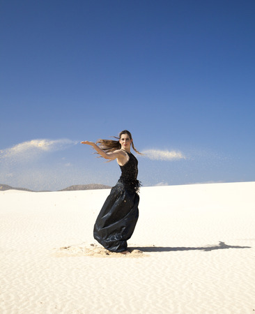 svelte: young attractive woman in black flamenco dress playing with the sand in dunes Stock Photo