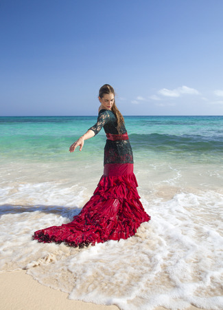 flamenco dress: young attractive woman in red and green  flamenco dress by ocean shore Stock Photo