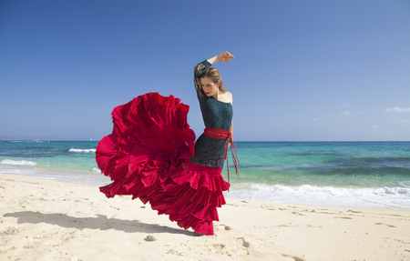 young attractive woman in red and green  flamenco dress by ocean shore Standard-Bild