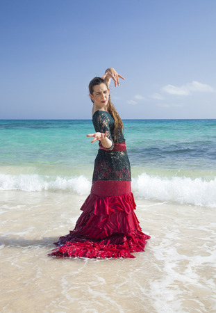 svelte: young attractive woman in red and green  flamenco dress by ocean shore Stock Photo