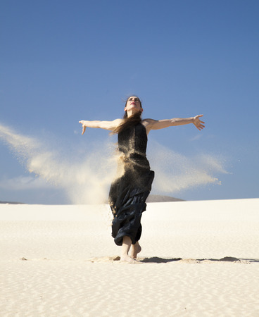 flamenco dress: young attractive woman in black flamenco dress playing with the sand in dunes Stock Photo