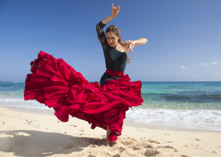 danseuse flamenco: jeune femme séduisante en robe de flamenco rouge et vert par l'océan rivage