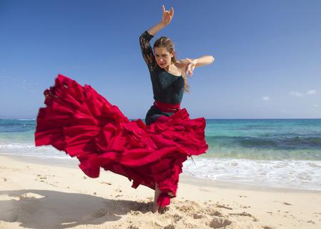 bailando flamenco: Mujer atractiva joven en traje de flamenca rojo y verde por la orilla del mar Foto de archivo