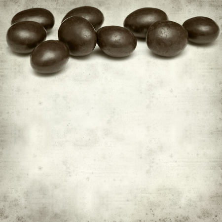 dragee: textured old paper background with chocolate coated almonds