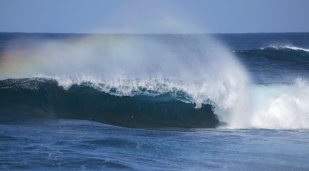 shores: powerful ocean waves with rainbow crest foam breaking by the shores of Gran Canaria Stock Photo