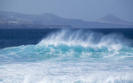 shores: powerful ocean waves breaking by the shores of Gran Canaria, Galdar mountain in the background