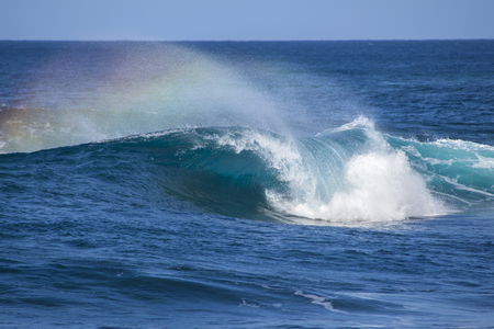 unstoppable: powerful ocean waves with rainbow crest foam breaking by the shores of Gran Canaria Stock Photo