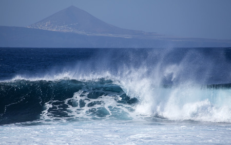 kinetic energy: powerful ocean waves breaking by the shores of Gran Canaria, Graldar mountain in the background