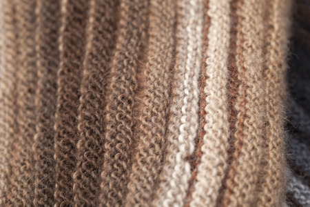gradual: two-sided ribbed knitted scarf, gradual color change, craft background
