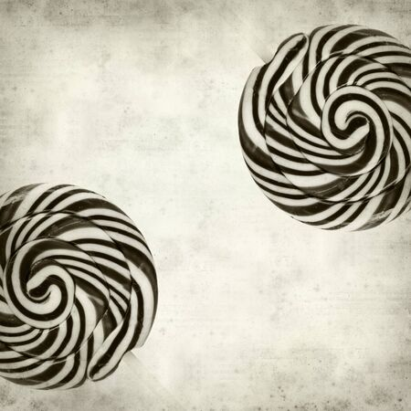 lolipop: textured old paper background with large black and white swirl lolipop Stock Photo