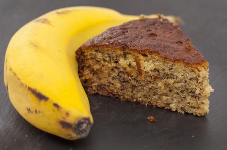 overripe: freshly made banana cake and overripe banana on black slate surface