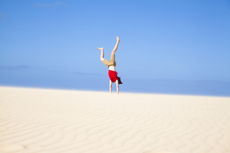 red tshirt: Fuerteventura sand dunes in the north of the island, teenage boy in red t-shirt making handstands