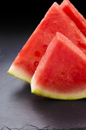 sliced watermelon: watermelon slices on black slate surface Stock Photo