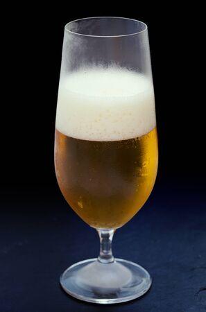 trivet: freshly poured glass of beer on black slate trivet Stock Photo
