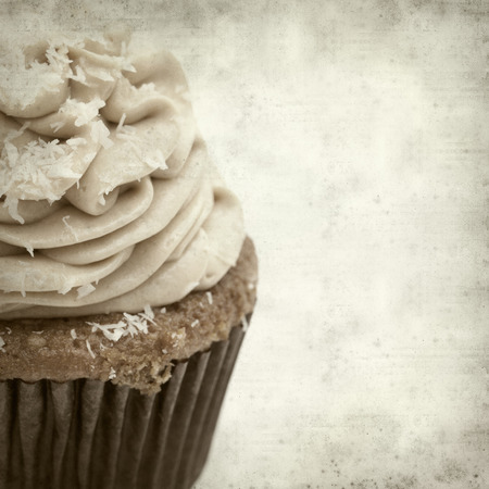 swirled: textured old paper background with cupcake with swirled icing Stock Photo