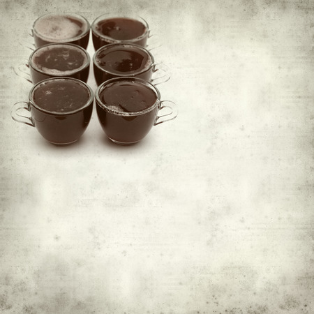 portions: textured old paper background with idividual strawberry jelly portions in glass coffeecups Stock Photo