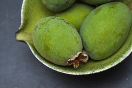 guava fruit: green feijoa fruit on black slate serving board