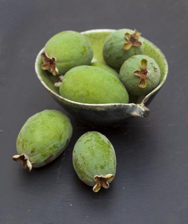green feijoa fruit on black slate serving board