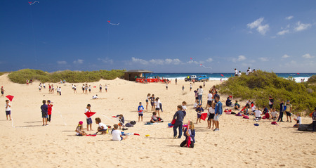 FUERTEVENTURA, SPAIN - NOVEMBER 11: School kids are trying to fly small kites at 29th International Kite Festival, November 11, 2016 in Dunes of Corralejo, Fuerteventura, Spain