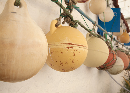 buoys: nautical decor - old fishning net buoys hang on outer wall of a house