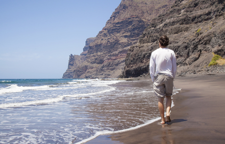 Gran Canaria,  beach Playa de Guigui in the western part of the island, accessible only on foot or by boat; young hiker walking along the waterline Stock Photo