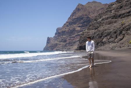 グラン ・ カナリア島、ビーチ、徒歩またはボートでのみアクセス可能な島の西部の部分でプラヤ デぐいぐい喫水線に沿って歩く若いハイカー 写真素材