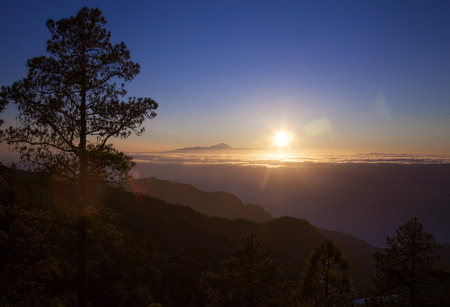 Gran Canaria,  late afternoon light over Teide on Tenerife, the peak of Teide  over the layer of clouds, ocean below Stock Photo