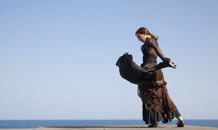 flamenco by ocean shore - young attractive woman in a long black dress dances, ocean and blue sky in the background