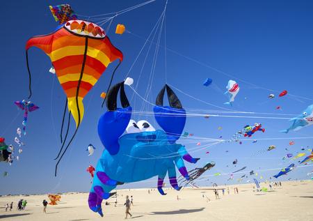 FUERTEVENTURA, SPAIN - NOVEMBER 11: Viewers watch from the ground as kites fill the sky at 30th International Kite Festival, November 11, 2017 in Nature park Dunes of Corralejo, Fuerteventura, Spain