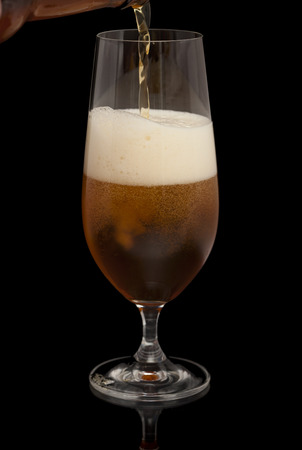 dark beer being poured into taster glass isolated on black Stockfoto
